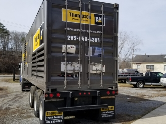 Rear view of Grey and yellow 52' trailer wrapped by sign source