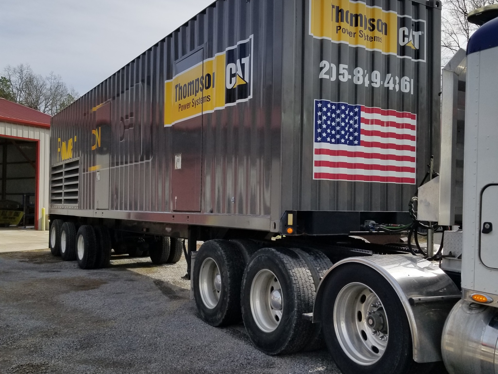 corner view of Grey and yellow 52' trailer wrapped by sign source