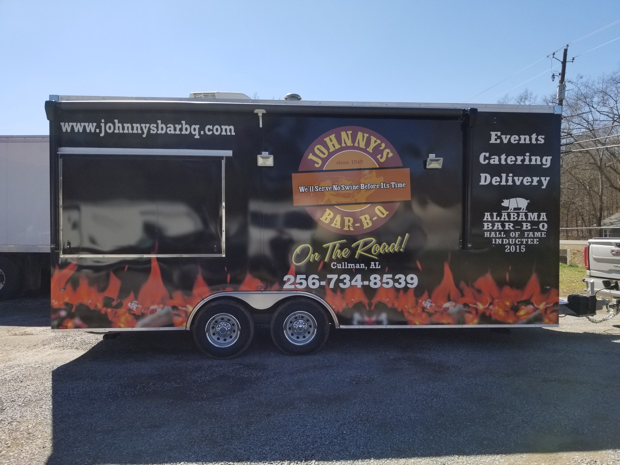 Wrapped food truck trailer colored orange and black from sign source