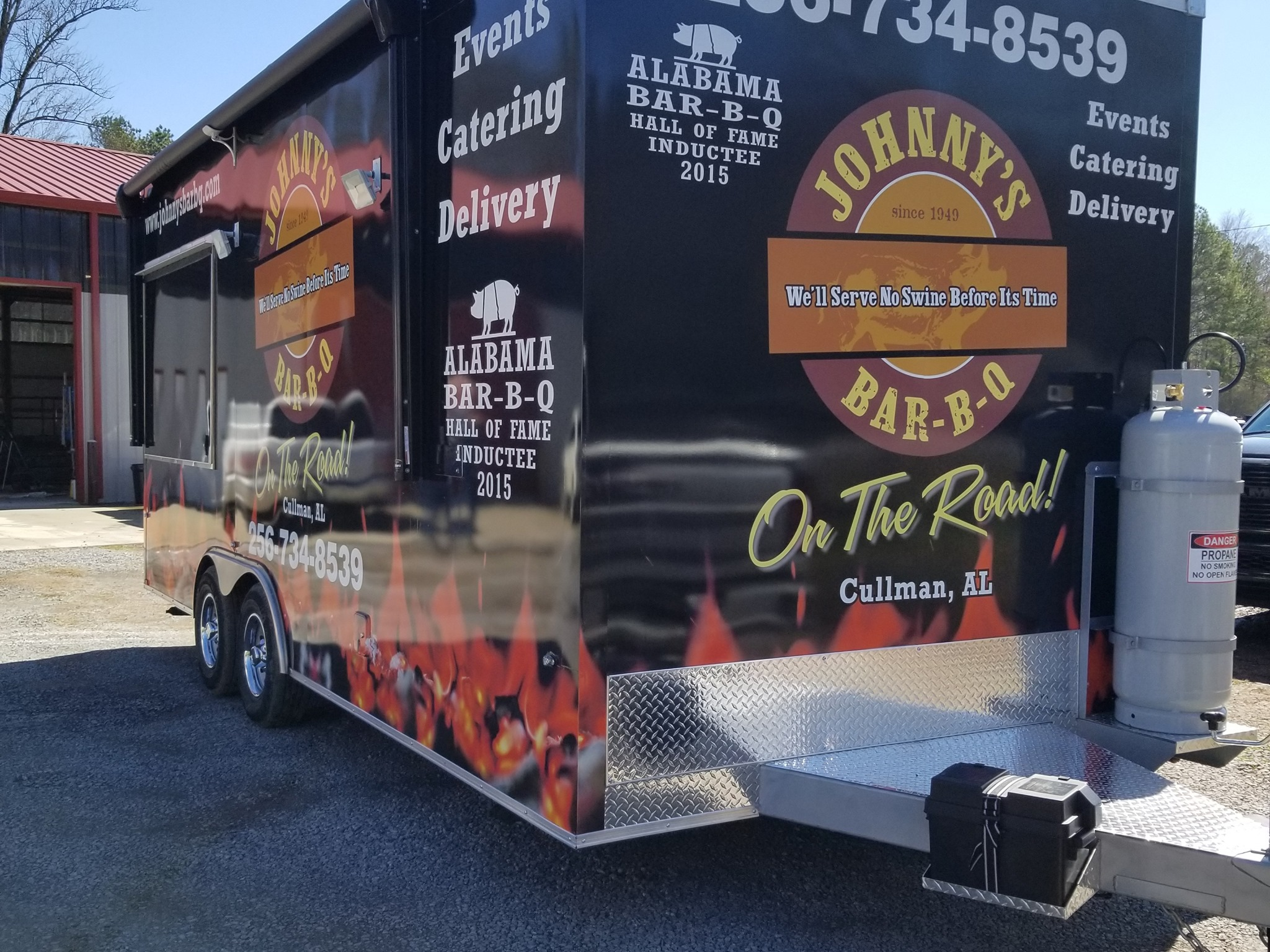 hitch view of Wrapped food truck trailer colored orange and black from sign source
