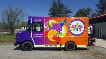 driver's side view of colorful wrap of food truck parked in sign source lot