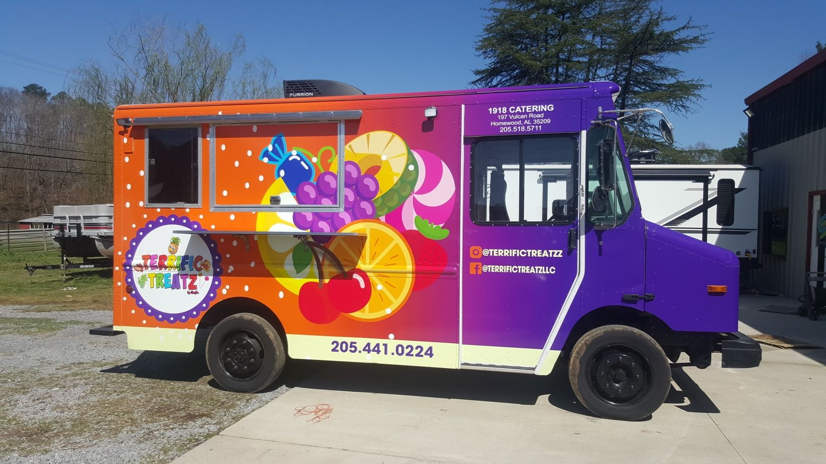 passengers's side view of colorful wrap of food truck parked in sign source lot