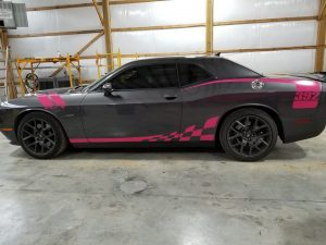 side of grey and pink dodge car wrapped with racing stripes